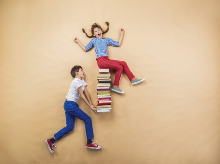 Happy children playing with group of books in studio