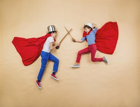 Kinderen spelen als superhelden met rode jassen