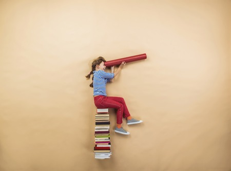 Happy girl is playing with group of books in studio Foto de archivo