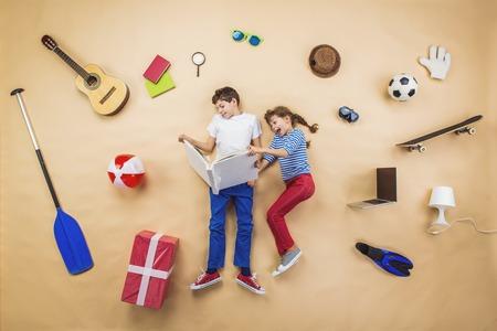 幸せな子供は彼らの周りのオブジェクトのグループを床に本を読んでいます。