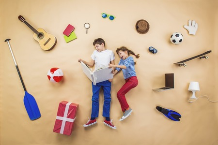 Happy children are reading book on the floor with group of objects around them