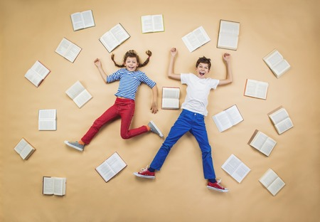boy book: Happy children lying on the floor with group of books