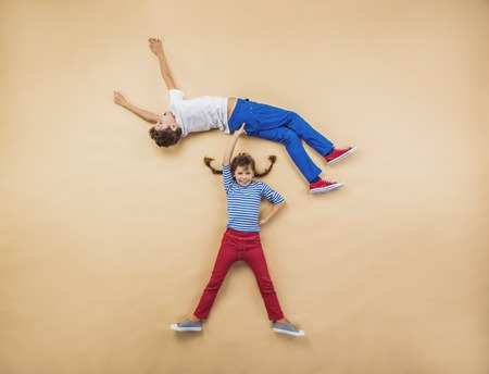 Funny children are playing together. Lying on the floor. Stock Photo