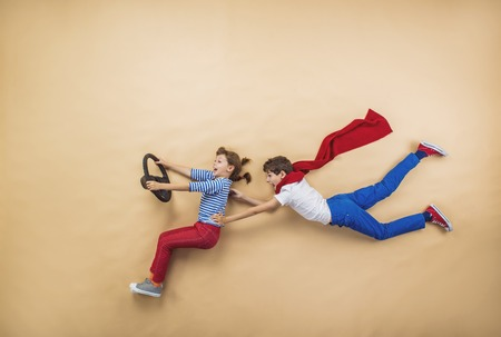 car concept: Funny children are playing together. Lying on the floor. Stock Photo