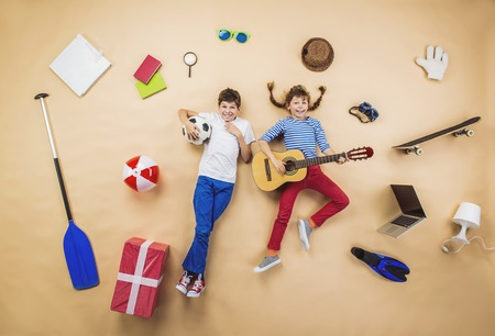 children playing together: Funny children are playing together. Lying on the floor with guitar and ball Stock Photo