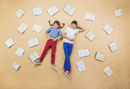 Happy children lying on the floor with group of books photo
