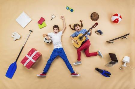 Grappige kinderen spelen samen. Liggend op de vloer met gitaar en bal