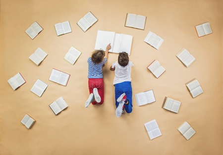 幸せな子供は、それらのまわりの本のグループと床に本を読んでいます。