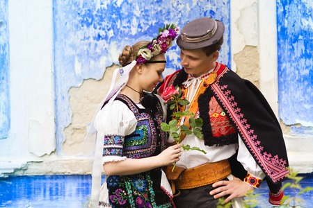 europe eastern: Love couple standing by the blue wall wearing traditional Eastern Europe folk costumes.