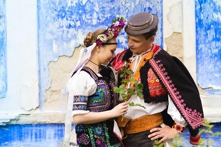 Love Paar stehend von der blauen Wand in traditioneller Osteuropa Trachten.