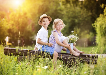kids hugging: Cute boy and girl in love. They sitting on bench at sunset.