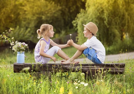 Cute boy and girl in love. They sitting on bench at sunset.