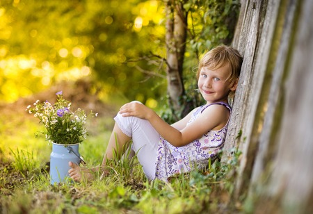 Little blonde girl holding meadow flowers laughing by the wooden fence photo