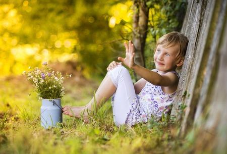 木の塀で笑って草原の花を保持している小さな金髪の少女 写真素材