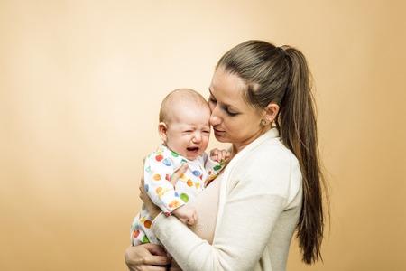 fille qui pleure: Enfant pleurant avec studio mère tourné sur fond beige Banque d'images