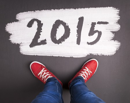 Happy new year 2015. Christmas concept with red sneakers and white chalk text on black floor photo