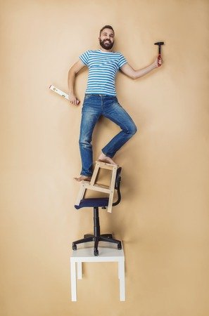 clumsy: Handyman standing dangerously on a pile of chairs. Studio shot on a beige background.