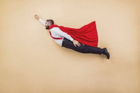 super powers: Manager in a flying pose wearing a red cloak. Studio shot on a beige background.