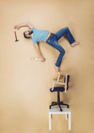 clumsy: Handyman falling dangerously from a high pile of chairs. Studio shot on a beige background.