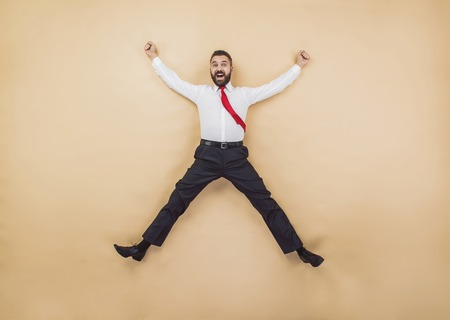 businessman jumping: Happy manager jumping high in a victorious pose. Studio shot on a beige background.