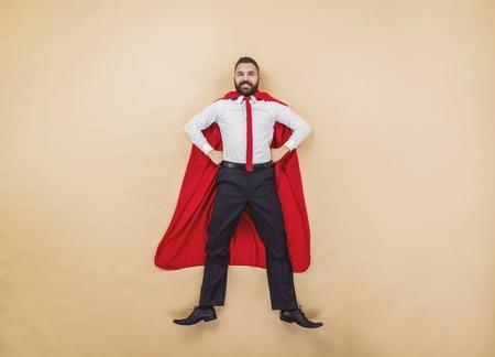 hombre fuerte: Gerente con una capa roja. Estudio tirado en un fondo beige.