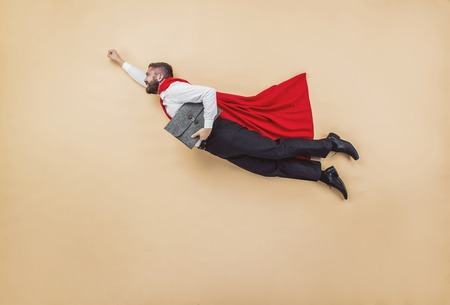 Manager dans un vol pose vêtu d'un manteau rouge. Tourné en studio sur un fond beige.