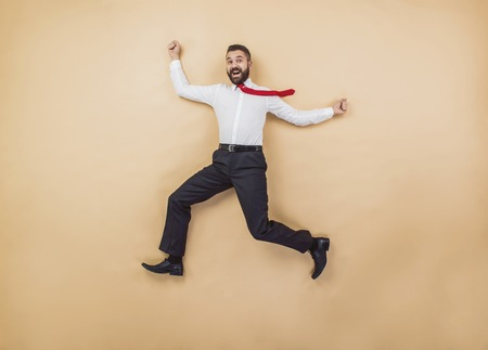 solver: Happy manager jumping high in a victorious pose. Studio shot on a beige background.