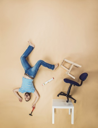 dangerously: Handyman falling dangerously from a high pile of chairs. Studio shot on a beige background.