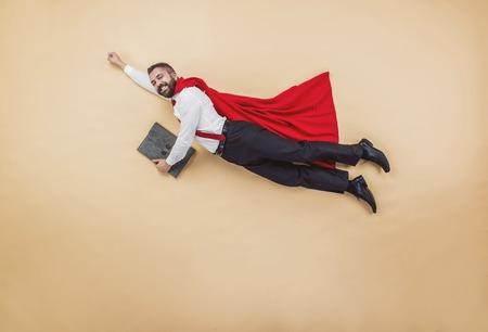 赤いマントを身に着けている飛行ポーズでのマネージャー。スタジオは、ベージュ色の背景で撮影。 写真素材