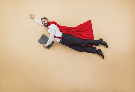 Manager in a flying pose wearing a red cloak. Studio shot on a beige background.