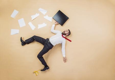 hombre cayendo: Gerente hermoso que tiene un accidente. Estudio tirado en un fondo beige. Actitud divertida. Foto de archivo