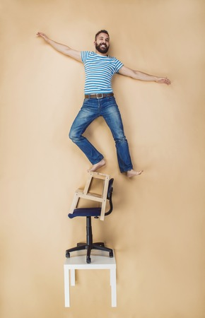 dangerously: Man standing dangerously on a pile of chairs. Studio shot on a beige background.