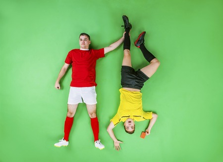 Referee giving red card to a football player. Studio shot on a green background. photo
