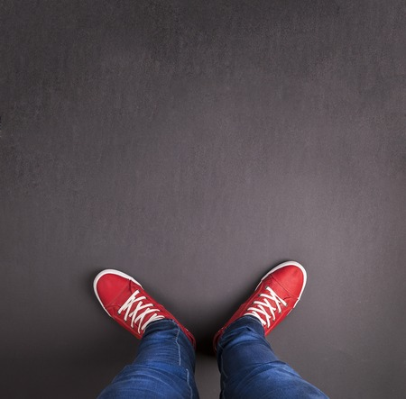 red jeans: Feet concept with red shoes on black background with blank space for text or symbol