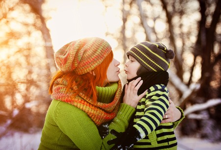 mom kiss son: Happy parents with child having fun outside in snow Stock Photo