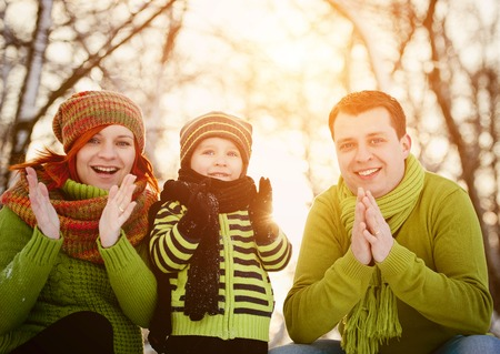 Happy parents with child having fun outside in snow photo