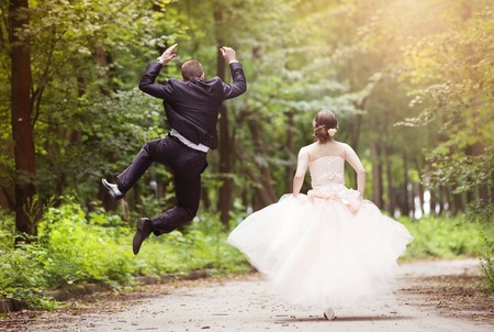 groom: Wedding couple - bride and groom - running down the road Stock Photo