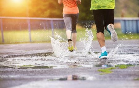 uomo sotto la pioggia: Giovane coppia fare jogging su asfalto in caso di pioggia