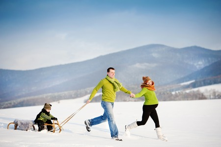 Happy parents with their son riding on sledge having fun outside in the snow. photo