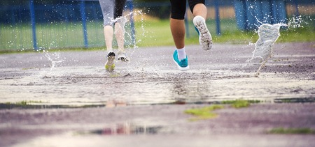 in: Young couple jogging on asphalt in rainy weather