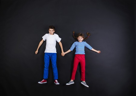 kids having fun: Playful young siblings laughing and having fun together. Studio shot on a black background.