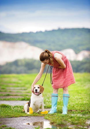 wellies: Young woman in dress and turquoise wellies walk her beagle dog in a park