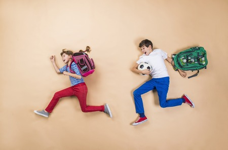 backpack school: Happy children running to school in a hurry. Studio shot on a beige background. Stock Photo