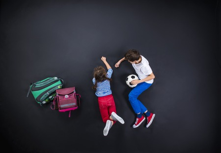 Hermanos jóvenes juguetones que se divierten juntos mientras se preparan para volver a la escuela. Estudio tirado en un fondo negro. Foto de archivo - 35429591