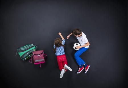 Speelse jonge broers en zussen plezier samen, die zich voorbereiden om terug te gaan naar school. Studio shot op een zwarte achtergrond.