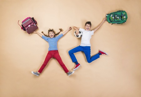 backpacks: Happy children running to school in a hurry. Studio shot on a beige background. Stock Photo