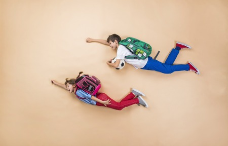 education: Happy children running to school in a hurry. Studio shot on a beige background. Stock Photo
