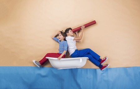 binoculars: Joyful kids as sailors on the sea. Studio shot on a beige background. Stock Photo