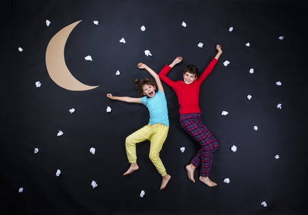 bedtime: Children getting ready for bedtime. Studio shot on a black background. Stock Photo