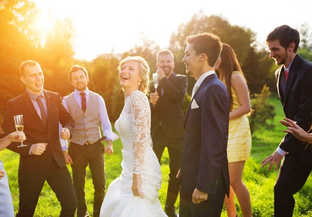 best party: Full length portrait of newlywed couple dancing and having fun with bridesmaids and groomsmen in green sunny park